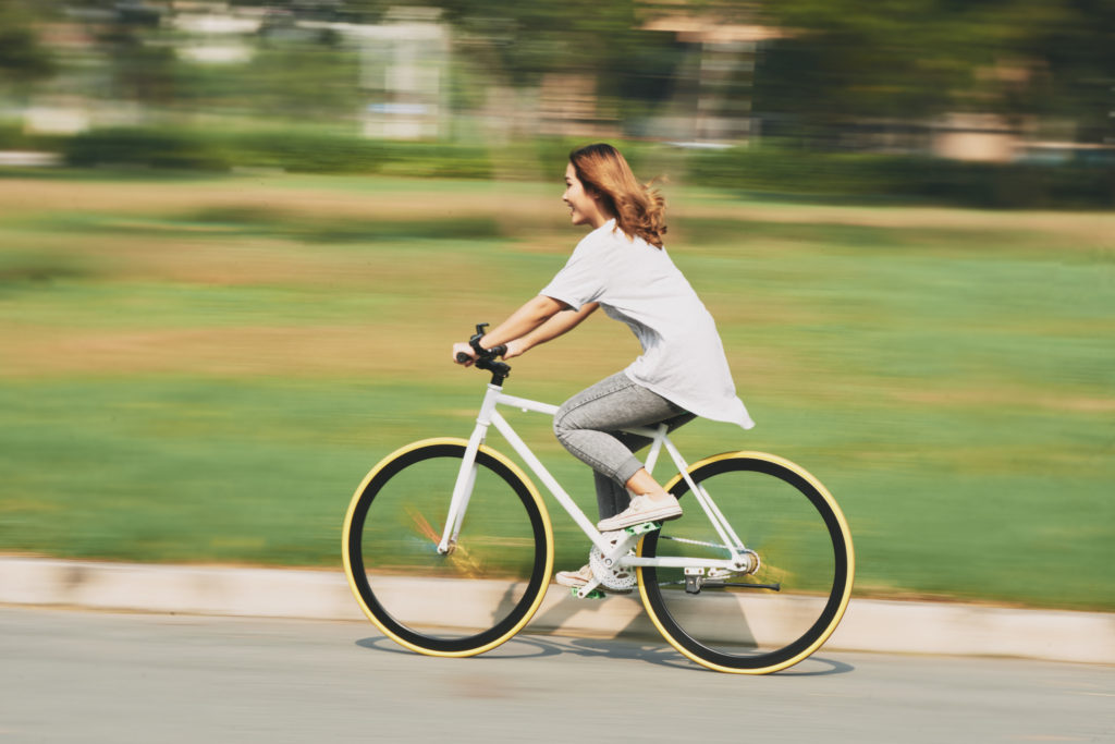 Happy excited young woman riding bicycle at high speed