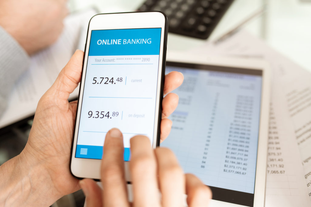 Hands of businessperson holding smartphone while scrolling through online banking account by workplace